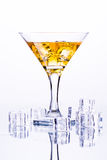 Martini glass with ice among ice cubes on white background Stock Image