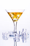 Martini glass with ice among ice cubes on white background Stock Photos