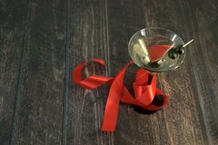 A martini glass with an olive and scarlet ribbon on a wooden table stock photo