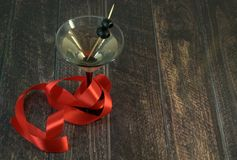 A martini glass with an olive and scarlet ribbon on a wooden table royalty free stock image