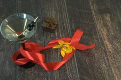 Martini glass with olives with a scarlet ribbon, gift box and yellow orchid on a wooden table stock photos