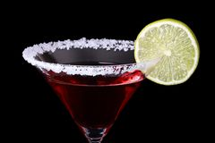 Martini. Glass of red martini with lime and sugar rim isolated on black Royalty Free Stock Photos