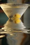 Martini Glass with Reflections. A ripe green olive sits at the bottom of a martini glass that is reflected in a liquid around the glass stock photography