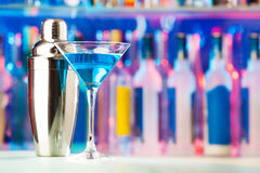 Martini glass and shaker standing on a bar counter Royalty Free Stock Image