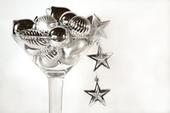 Martini glass of silver christmas ornaments. Martini glass brimming with silver Christmas ornaments with two stars hanging off the side. Close up on white stock photography