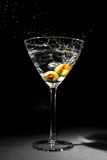 Martini Glass with Two Splashing Olives. Photo of a full martini glass with clear liquid and two olives with pimentos splashing into its contents Stock Images