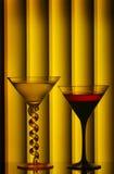 Martini glasses. Two martini glasses arranged against dim light stripe background Stock Image