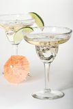 Martini glasses with cocktails. Closeup of martini glasses with cocktails over paper background served with lime and decorative umbrella Stock Photography