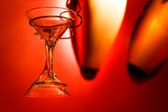 Martini glasses hanging with red background. Two martini glasses hanging with a strong red color background Stock Photo