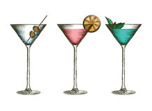 Martini glasses with olives, citruses and leaves of mint. Glass goblets with colorful cocktails in engraved style. stock illustration
