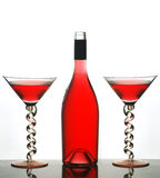Martini glasses and red wine. Red wine in bottle and two martini glasses with spiral stems, white studio background Stock Photography