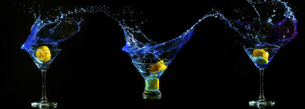 Martini glasses with splashing blue water Stock Photos