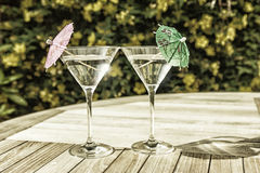 Martini glasses in the summer sunshine. Landscape colour photo of a pair of martini cocktail glasses on a pub garden table sparkling in the summer sunshine Royalty Free Stock Images