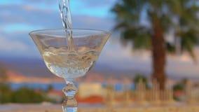 Martini h?lls in i ett exponeringsglas p? en bakgrund av havet stock video