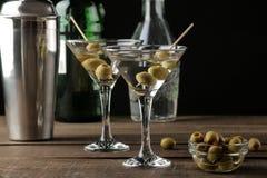 Martini i en exponeringsglasvinglas med gröna oliv på en steknål på en brun trätabell coctailar stång arkivfoton