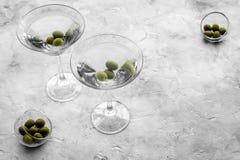 Martini koktajl w szkle z oliwkami przy dnem na popielatym kamiennym tło odgórnego widoku copyspace Fotografia Royalty Free