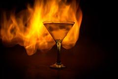 Martini nel concetto del fuoco Vetro della combustione famosa di Martini del cocktail in fuoco a fondo nebbioso tonificato scuro fotografie stock libere da diritti