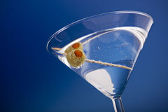 Martini with olive. Pimento stuffed olive in a martini cocktail on blue background Stock Image