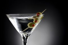 Martini and olives. Close up shot of Martini with tooth pick and green olives, shot on black background with space for copy royalty free stock images