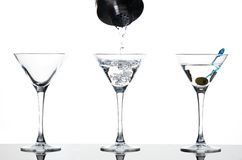 Martini pouring. Three martini glasses - empty, being poured and full with olive Stock Photos