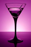 Martini in purple. Martini glass on table in purple light Stock Images