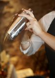 Martini shaker. Hands of bartender in motion shaking up martini shaker stock photography