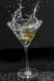 Martini Splash. Splashing dirty martini garnished with green olives on toothpick Royalty Free Stock Image