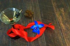 Martini szkło z oliwkami z szkarłatnym faborkiem, prezenta pudełkiem i błękitną orchideą na drewnianym stole, obraz stock