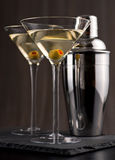Martini. A traditional wet martini with olive and cocktail shaker Stock Image