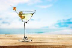Martini in vetro con le olive su fondo vago Fotografia Stock