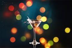 Martini in vetro con le olive sul fondo del bokeh Immagini Stock