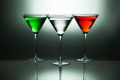 Martinis and Cosmopolitans. Three martinis and cosmopolitans illuminated under glowing light Stock Image