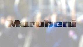 Marubeni Corporation logo on a glass against blurred crowd on the steet. Editorial 3D rendering. Marubeni Corporation logo on a glass against blurred crowd on stock footage
