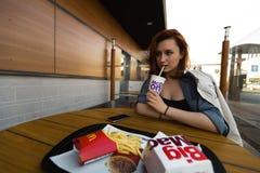 MARUPE, LETONIA - 22 DE ABRIL DE 2019: Mujer joven que bebe el caf? de McDonalds al aire libre en un campo durante puesta del sol fotos de archivo libres de regalías