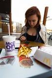 MARUPE LETTLAND - APRIL 22, 2019: Ung kvinna som utomhus dricker McDonalds kaffe i ett f?lt under solnedg?ng royaltyfria foton
