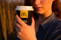 MARUPE LETTLAND - APRIL 22, 2019: Ung kvinna som utomhus dricker McDonalds kaffe i ett f?lt under solnedg?ng fotografering för bildbyråer