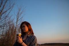 MARUPE LETTLAND - APRIL 22, 2019: Ung kvinna som utomhus dricker McDonalds kaffe i ett f?lt under solnedg?ng arkivfoto