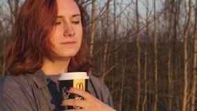 MARUPE, LETTONIE - 22 AVRIL 2019 : Jeune femme buvant du café de McDonalds dehors dans un domaine pendant le coucher du soleil banque de vidéos