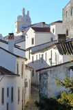 MARVAO, PORTUGAL: A typical cobbled street with whitewashed houses and tiled roofs with the Clock Tower in the background Royalty Free Stock Photo