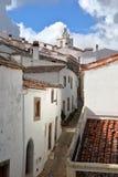 MARVAO, PORTUGAL: Uma rua cobbled típica com casas whitewashed e os telhados telhados com a torre de pulso de disparo no fundo fotos de stock
