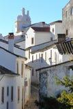 MARVAO, PORTUGAL: Uma rua cobbled típica com casas whitewashed e os telhados telhados com a torre de pulso de disparo no fundo Foto de Stock Royalty Free