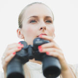 Marveling. Young woman holding binoculars and surveying Royalty Free Stock Images