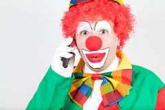 Marvelling clown with smartphone Royalty Free Stock Photos