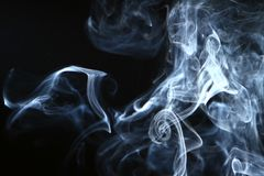 Marvellous swirl contrast blue smoke against dark background. Marvellous flowing contrast blue smoke on heavy black background royalty free stock images