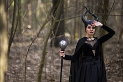Marvellous and Magical Maleficent Woman with Horns Posing in Spring Empty Forest with Crook. Horizontal Image stock image