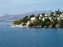 Marvelous blue water Aegean coast with rich nature, mountains and small white houses.  royalty free stock images