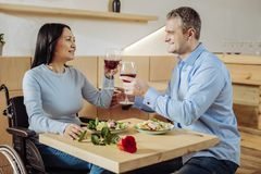 Disabled woman receiving compliments. Marvelous dinner. Disabled pretty lady receiving compliments while having a conversation with a man stock photos