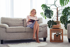 Marvelous female with charming smile reading book Stock Photography