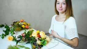 Marvelous female floral decorator looks at camera and smiles, s royalty free stock photography