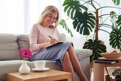 Marvelous female writing letter while sitting on sofa Stock Photography